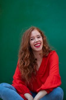 Стильная рыжая женщина позирует с зеленым фоном