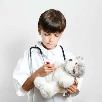 Прелестный милый мальчик держит плюшевого мишку