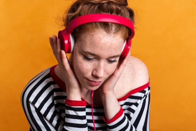 そばかすと赤いヘッドフォンでクローズアップ女性