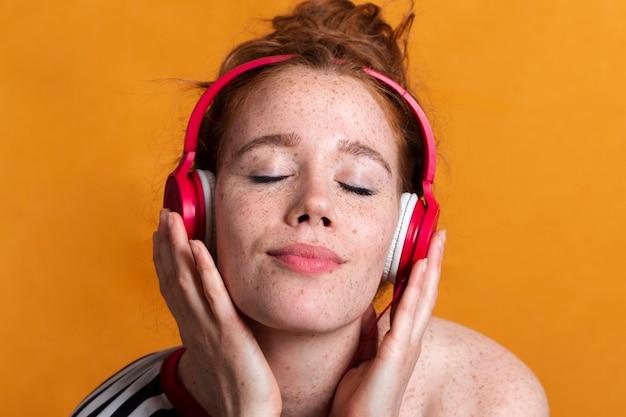 ヘッドフォンとオレンジ色の背景を持つクローズアップのきれいな女性