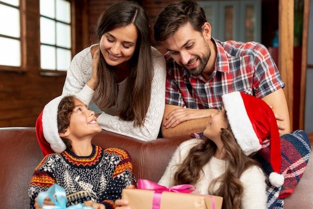 Средний снимок счастливые родители смотрят на своих детей