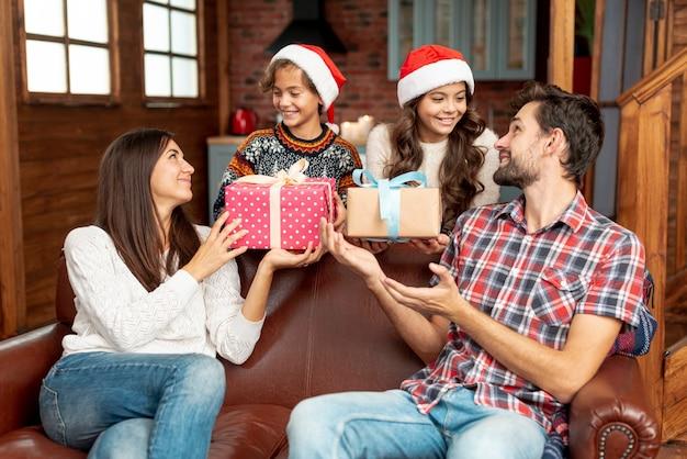 プレゼントで両親を驚かせるミディアムショットの子供