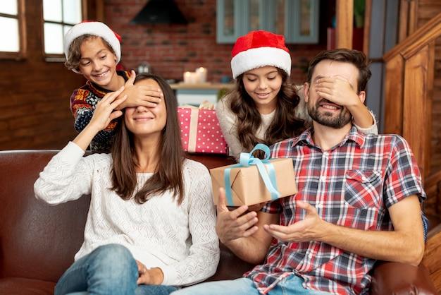 両親をプレゼントで驚かせるミディアムショットの子供