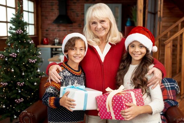 Средний снимок счастливая бабушка позирует с внуками