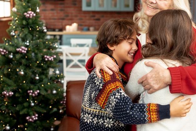 Крупным планом счастливая бабушка обнимает внуков
