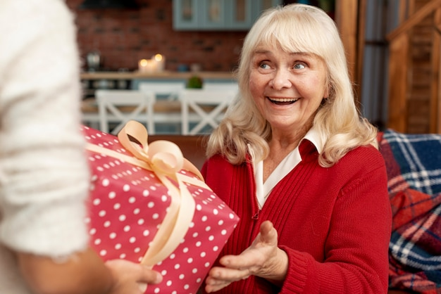 Крупным планом счастливая бабушка получает подарок