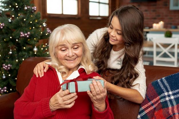 おばあちゃんに贈り物を提供するミディアムショットの孫娘