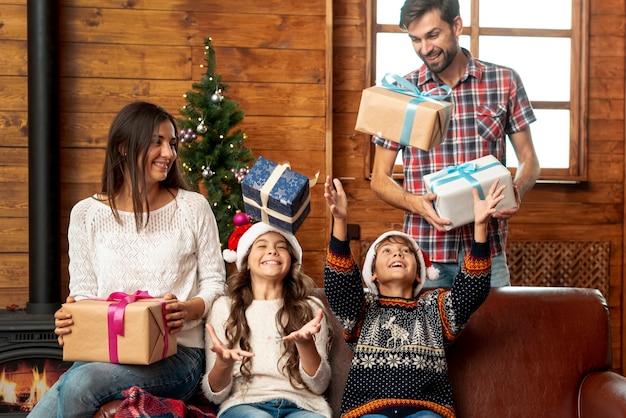 子供たちをプレゼントで驚かせるミディアムショットの両親