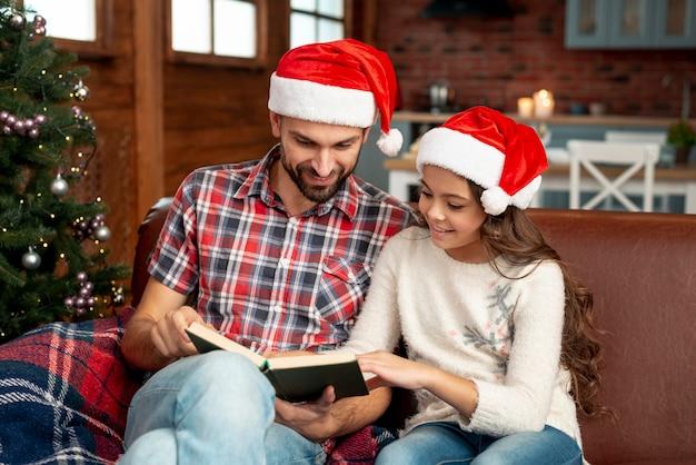 ミディアムショットの父と娘が一緒に読んで