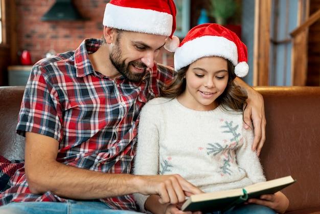 ミディアムショットの父娘に本を見せて