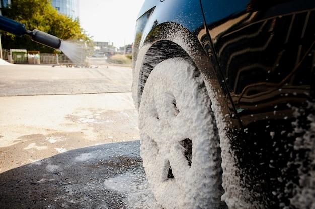 Колесо автомобиля покрыто мыльной пеной