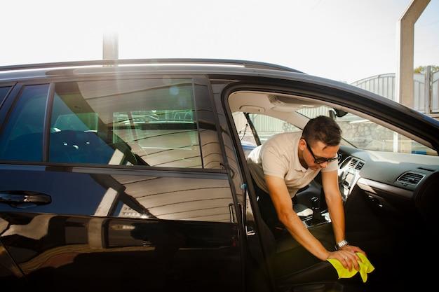Мужчина чистит сиденье черной машины