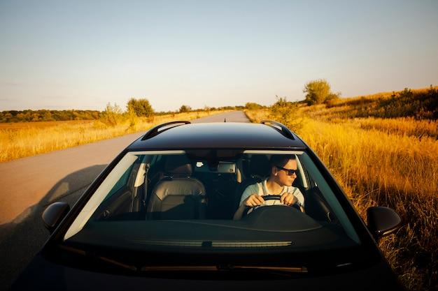黒い車を運転する男