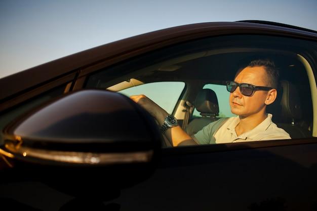 道路を見ている運転の男