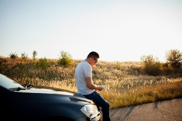 車のボンネットで休む若い男