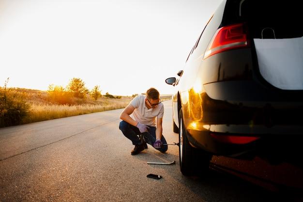 Молодой человек меняет колесо автомобиля