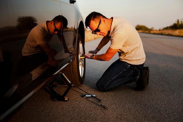 Мужчина снимает колесо с машины