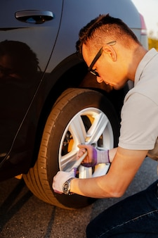 若い男が車のホイールを修正