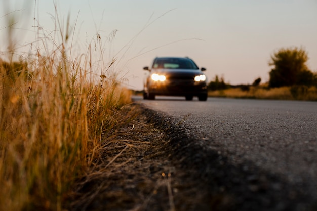 Черная машина едет по дороге