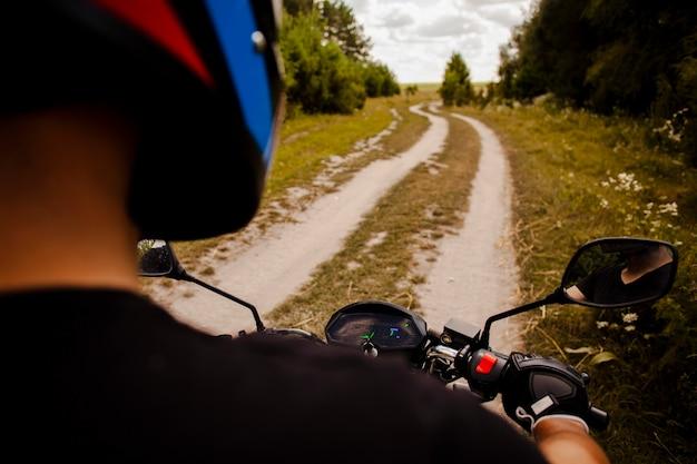 Человек ехал на мотоцикле по грунтовой дороге