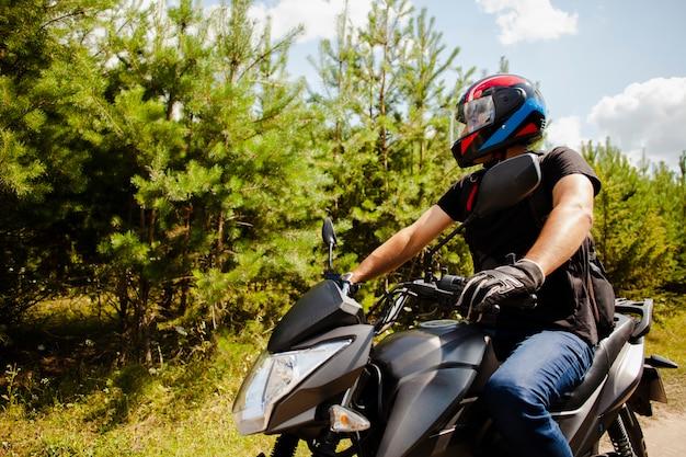ヘルメットと未舗装の道路でバイクに乗る男