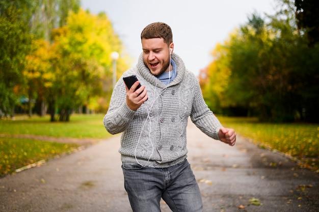 Человек с смартфон и наушники на аллее в парке