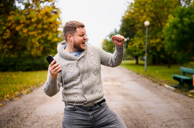 Молодой человек танцует осень в парке