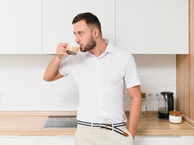 Молодой человек в футболке, попивая кофе на кухне