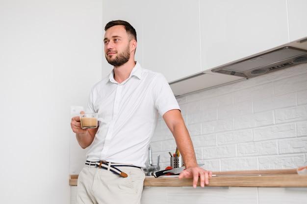 コーヒーを片手にハンサムな若い男