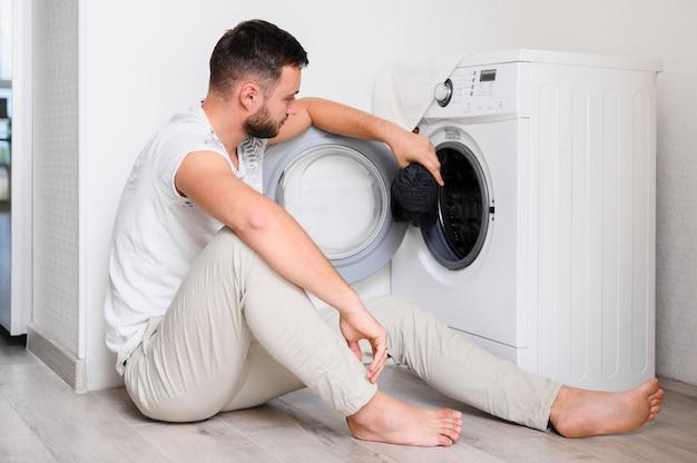 Молодой человек кладет одежду в стиральную машину