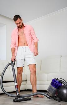 部屋で掃除機を持つ若い男