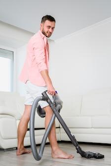 部屋の寄木細工の床を志す若い男