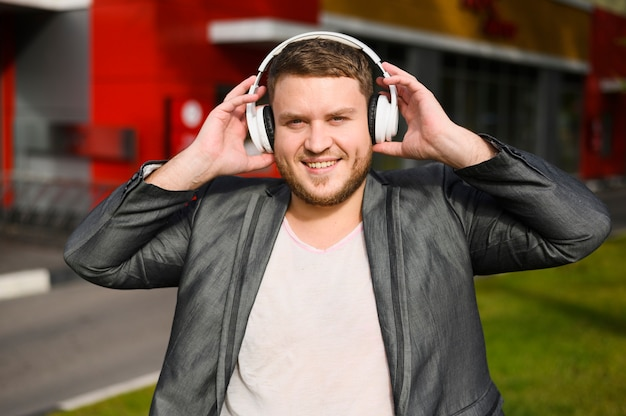 彼の耳にヘッドフォンで幸せな若い男