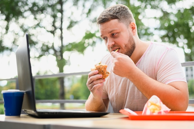 ノートパソコンを見ながら食べる若い男