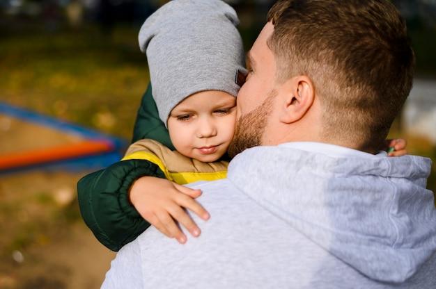 若い男が彼の腕の中で少年を保持
