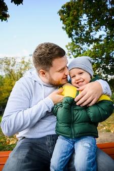 Молодой человек держит мальчика на ноге