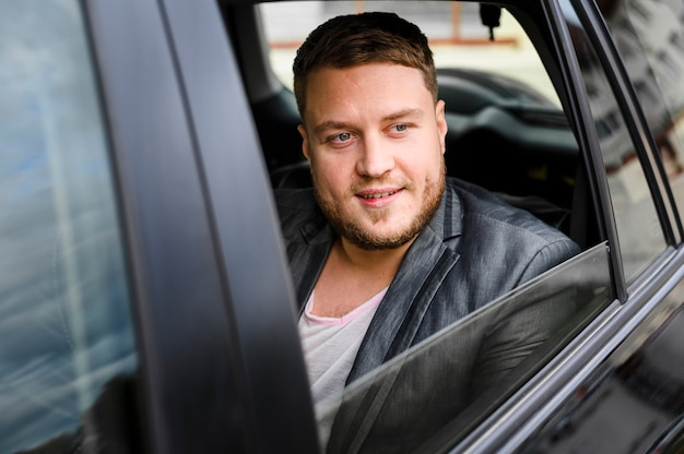 窓を開けて車の中で若い男