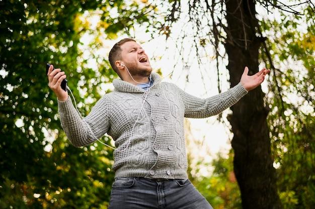 スマートフォンと公園でイヤホンを持つ男