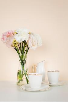 花の花束の横にあるティーカップ