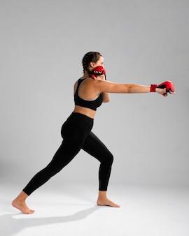 Женщина вида сбоку в одежде для фитнеса, пробивая с перчатками коробки