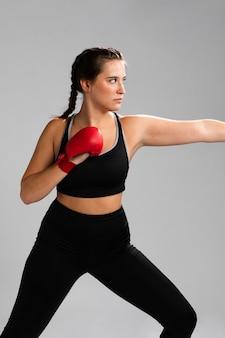 Боком женщина, одетая в фитнес-одежду готова дать удар