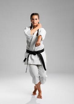 黒帯と空手の練習着物を持つ女性の全身ショット