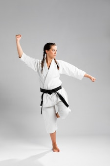 Женщина каратэ в действии изолированная на белой предпосылке