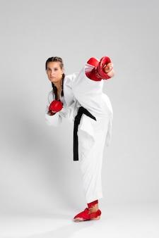 白い背景の上の箱の手袋を持つ女性の全身