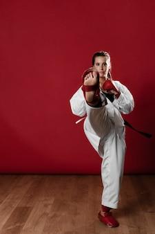 Полная длина выстрел женщины с черным поясом и кимоно, занимающихся каратэ
