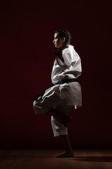 Боком женщина в белой форме каратэ