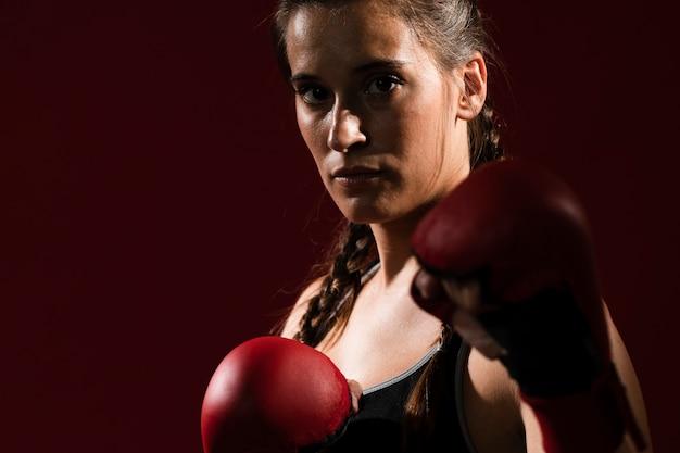 フィットネスの服と箱の手袋で運動の女性