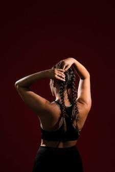 後ろから髪の三つ編みの尾を修正する女性