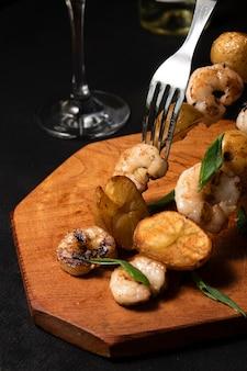 Закрыть вверх креветки и картофельные шашлычки