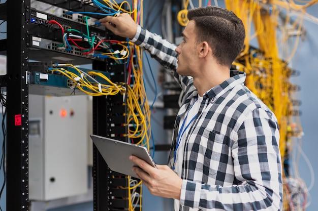 Молодой инженер работает в серверной комнате с планшета